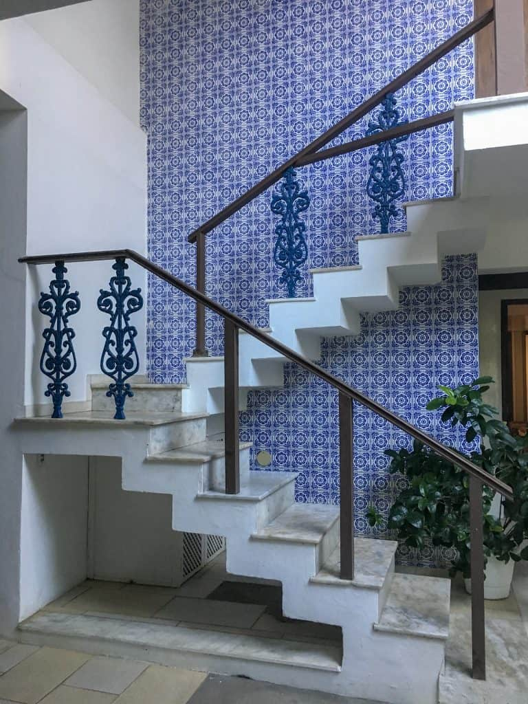 Staircase in front of blue and white tile wall