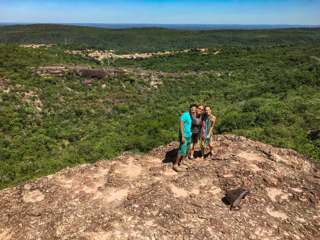 three hikers on the top of a limestone plateau surrounded by green valleys